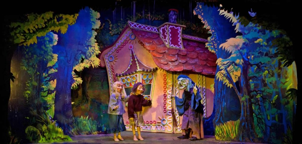 The witch invites Hansel and Gretel inside